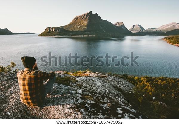 Mann allein sitzen und Meer- und Bergblick Reisen Lifestyle Abenteuer Outdoor Sommerferien Wildnis Natur