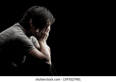 Alleinstehende Person, die traurig ist, bereut oder fürchtet sich und gibt ihr Gesicht auf dunkelschwarzem Hintergrund ab