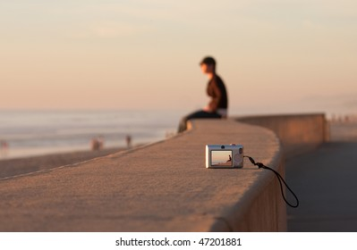 Man sitting alone on a concrete walkway near the ocean beach.  Sunset.  Taking a picture of himself placing the camera on timer on the concrete.  Face blurred, Focus on camera