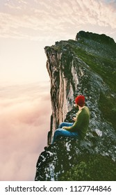 Man sitting alone on the edge mountain ridge above clouds travel adventure lifestyle extreme vacations