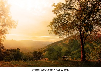 Man sitting alone watching yellow and orange setting sun in distance on a high mountain.