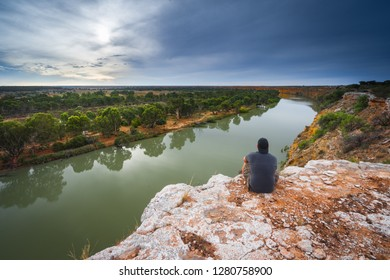 Man sitting atop cliffs looking over the Murray River