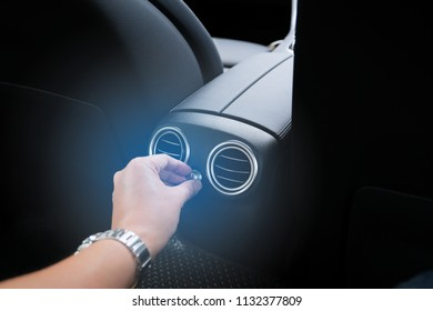 Man sitting in back car seat and adjustment small knob to control volume of rear air condition in luxury car.