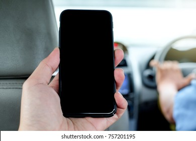 Man sitting in back seat of taxi and left hand holding Cellphone for use mobile application.