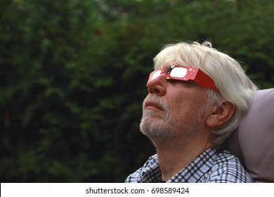 Man sitting in the backyard wearing solar eclipse glasses, looking up at the sky