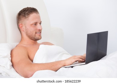 Man sitting up in bed against the pillows working on a laptop computer smiling as he reads the screen