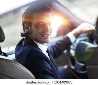 man sitting behind the wheel of a car