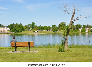 Man sitting in the bench facing the lake