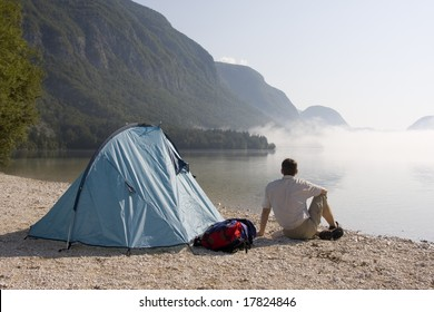 Man sitting beside his tent at a mountain lake