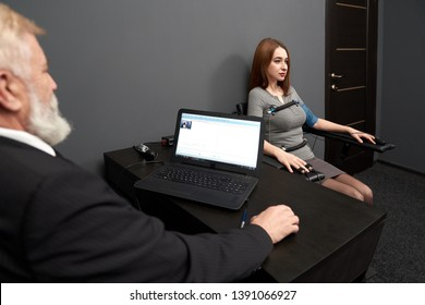 Man sitting at black table and looking at computer polygraph, monitoring amplitude, pulse of woman. Concentrated woman sitting at chair, testing with polygraph. Sensors on finger, hands and body.