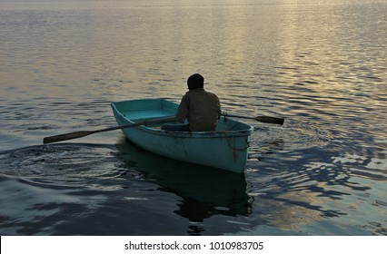 A man sitting in a blue rowing boat.