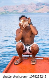 A man sitting at the boat and  blowing on a conch shell at Coron island Philippines
