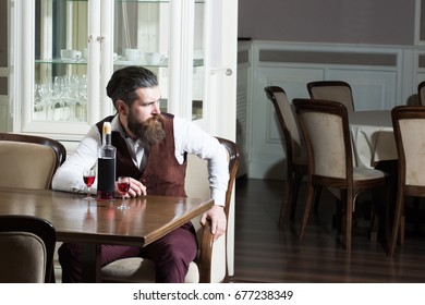 Man sitting with bottle of wine and two glasses on table. Bearded hipster with beard in brown vest in restaurant. Alcohol and appetizer. Unhealthy lifestyle and bad habits