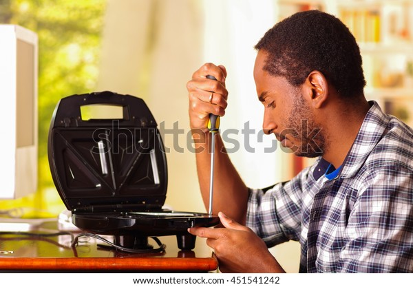 Man sitting by desk repairing sandwich maker using screwdiver, serious facial expressions while working
