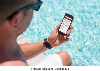 Man sitting by the pool and checking email on his smartphone
