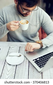 Man sitting at cafe bar, drinking morning coffee and looking at watch.