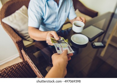 man sitting in the cafe gives money to another man