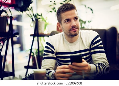 Man sitting at cafe with smart phone in his hands. Shallow depth of field.