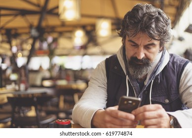 Man sitting at cafeteria or restaurant holding smartphone, looking at its screen.