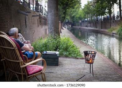 Man sitting with campfire next to Nieuwe Gracht, Utrecht, Netherlands, september 2019