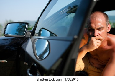 Man sitting in the car with hand on his mouth and thinking.