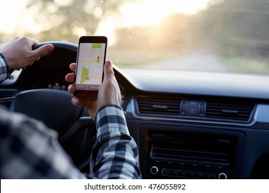 Man sitting in the car and holding black mobile phone with map gps navigation