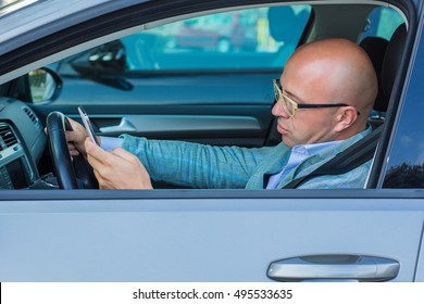 Man sitting in car with mobile phone in hand texting while driving. Distracted guy checking his smart phone not paying attention reading text message email outdoors background