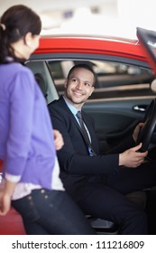 Man sitting in a car while talking to a woman in a car shop