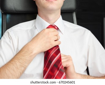 The man sitting in the chair, adjusts his red tie.