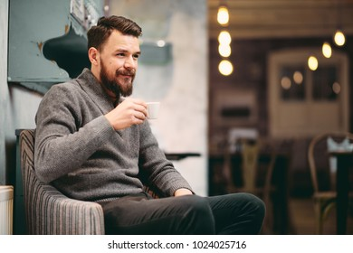 Man sitting in the chair and drinking coffee at cafe