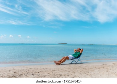 Man is sitting in chair on a tropical beach. Summer vacation concept.