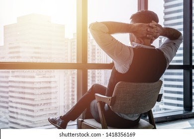 Man sitting comfortably on the chair with hands behind his head looking outside through the window indoors.