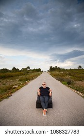 Man sitting in a couch in the middle of a road