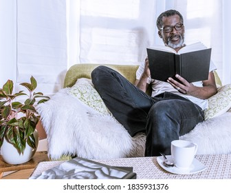 A man sitting in a couch is reading a book