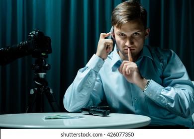Man sitting in dark interior, talking on cellphone, money and gun lying on table