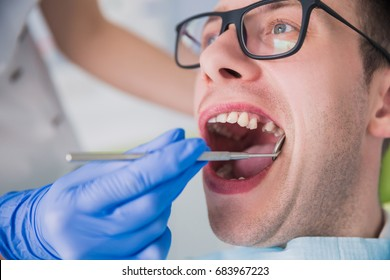 man sitting at a dentist's office at a dentist's office without one tooth