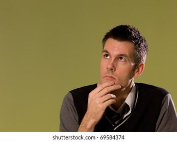 A man sitting at a desk and holding his chin as if thinking