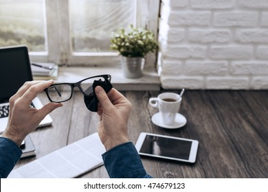 Man sitting at desk at home and cleaning his glasses with a cloth