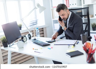 A man is sitting at the desk at the office, talking on the phone, holding a marker in his hand and counting on a calculator.