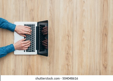 Man sitting at desk and working with a computer, he is typing and networking
