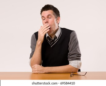 A man sitting at a desk and yawning
