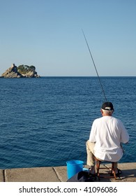 Man sitting at the dock, against the island, and angling.