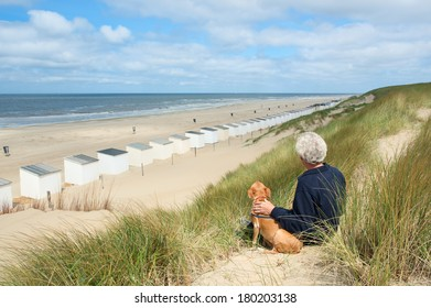 Man sitting with dog in the dunes and looking to the huts