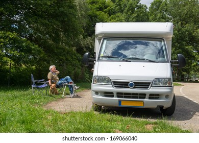 Man sitting with dog having a break with mobil home