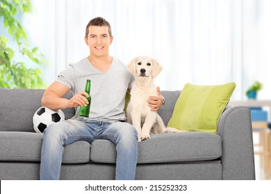 Man sitting with dog on couch and holding beer at home