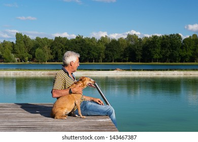 Man sitting with dog on pier at a lake