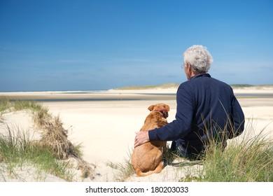Hombre sentado con perro en una duna de arena en la playa holandesa en la isla de wadden Texel