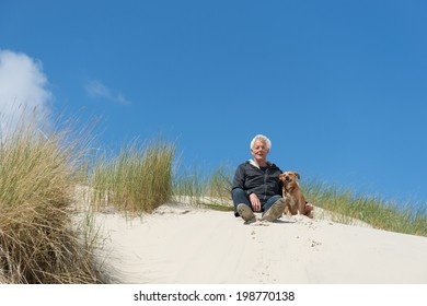 Man sitting with dog on top of the dunes