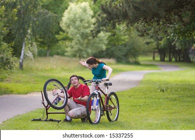 A man, sitting down, attempts to fix his bicycle, while it is upside-down and explaining it to the woman. The woman stands behind him, watching. - horizontally framed