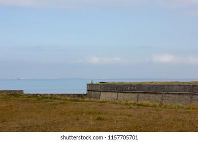 Man sitting at Fortress of Vauban by the sea, France